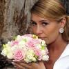 Svadobná fotografia očarujúca nevesta s peknou svadobnou ružou a pekným svadobným účesom.